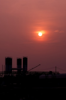 Beautiful sun and the red sky over the silhouette industrial factory.
