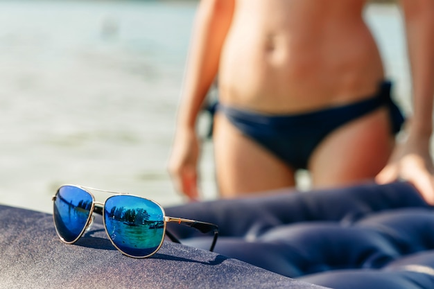 Beautiful sunglasses in gold rim against the  of a blurred girl in a bikini. the  of vacation, vacation, summer, vacation, travel. copyspace.