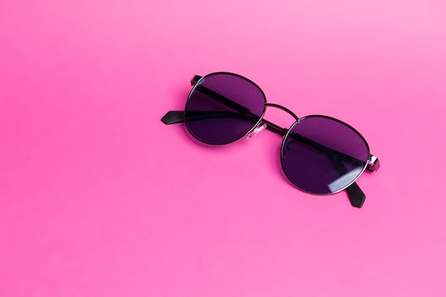 Beautiful sunglasses on pink isolated background close-up