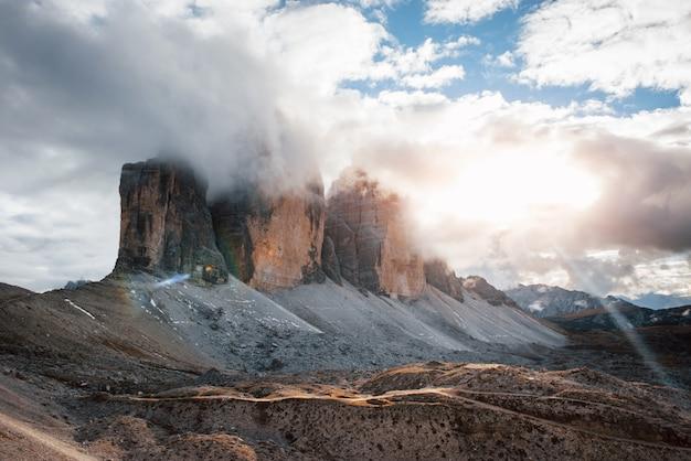 Красивый солнечный свет создает красочный пейзаж. горы в тумане и облаках. tre cime di lavaredo.