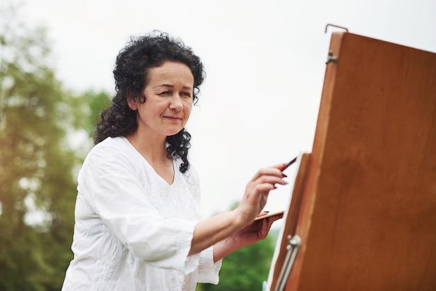 美しい日光。屋外の公園で黒い巻き毛を持つ成熟した画家の肖像