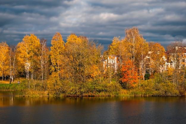 湖の美しい日当たりの良い秋の海岸の風景。黄金の秋の木の背後にある豊かな邸宅。 Premium写真