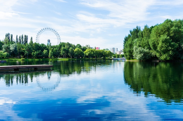 Beautiful sunny cityscape scene of green park with ferris wheel and lake in the center of megapolis
