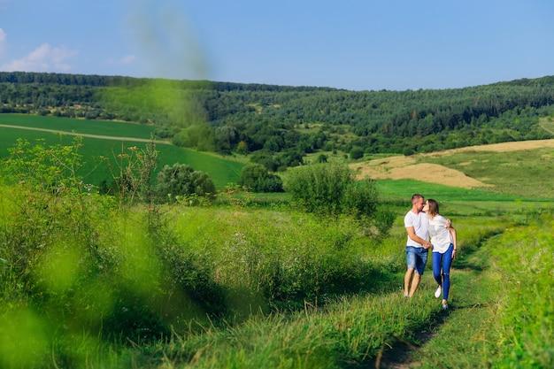 Прекрасный солнечный день. луг с зеленой травой и лесом. влюбленная пара гуляет и целуется.