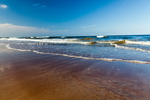 Beautiful sunny weather on the baltic sea coast, cold summer weather on the baltic sea coast, seascape on the sea on a sunny day with blue sky and lots of waves on the water
