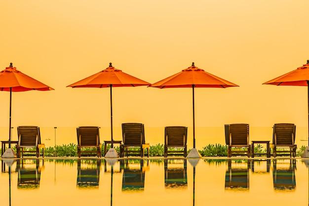 Beautiful sunrise around with umbrella and chair outdoor swimming pool
