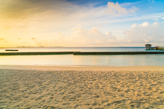 Beautiful sunrise over beach with the water villas in tropical maldives island .