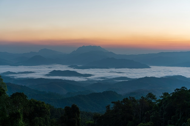 Beautiful sunrise and colorful sky in the mist over the mountain