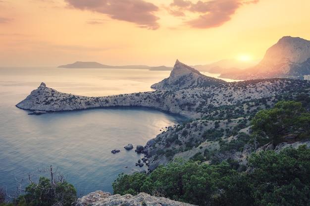 Красивый восход солнца в горах у моря. удивительный летний пейзаж со скалами, горный лес, красочное ярко-оранжевое небо с солнцем, голубая вода по утрам. морской пейзаж на рассвете. природа фон