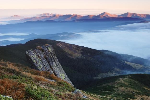 산에서 아름 다운 일출입니다. 떠오르는 태양에 비추어 아침 안개와 산맥이 있는 가을 풍경