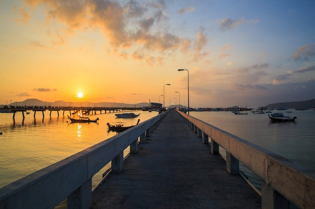 Beautiful sunrise and landscapes of the concrete bridge pier with boats during the sunrise summer travel in phuket