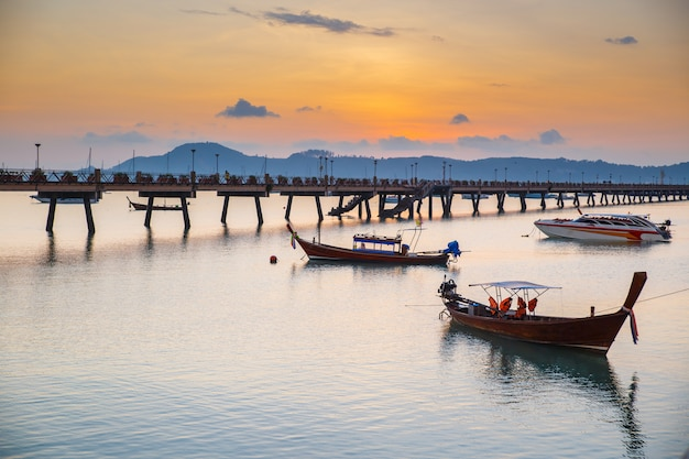 Beautiful sunrise and landscapes of the wooden bridge pier with boats during the sunrise summer travel in phuket, thailand.