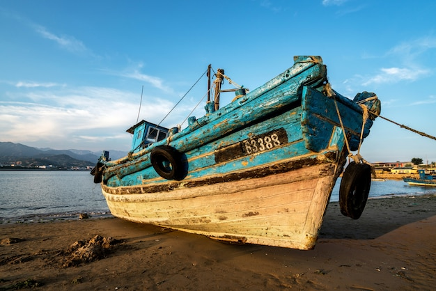 Beautiful sunrise on an old wooden fishing boat on the beach