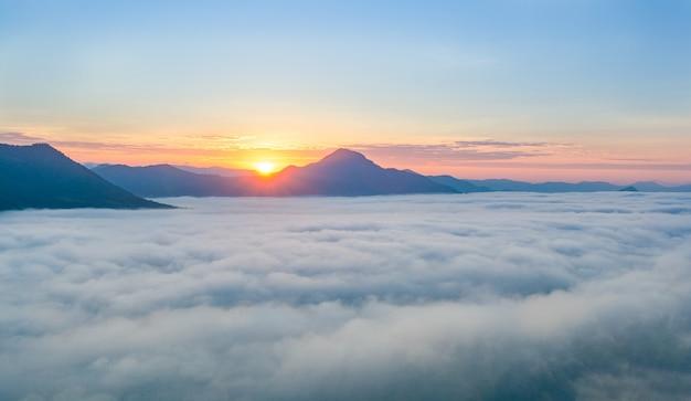 아침에 안개로 산 위에 아름다운 일출