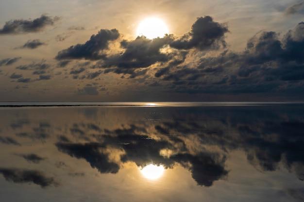 Красивый восход солнца над индийским океаном на острове занзибар, танзания, восточная африка. концепция путешествия и природы. утреннее небо, облака, солнце и морская вода