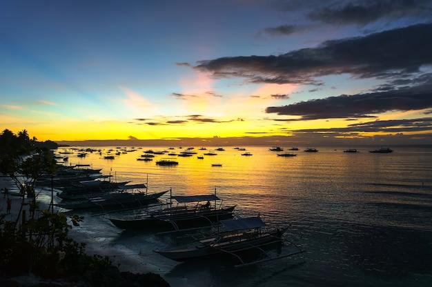 フィリピンの漁船を背景に海から昇る美しい日の出、黄色と紫の色