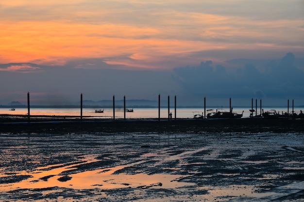 干潮時に水中で空の反射と海の桟橋の上の美しい日の出のシーン