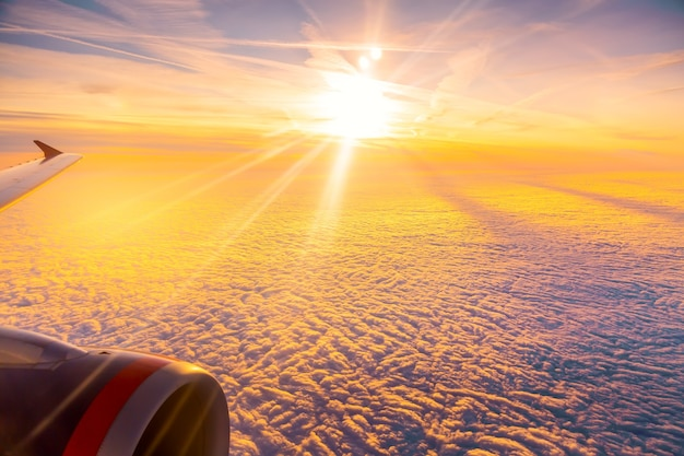Beautiful sunrise sky above clouds with aircraft wing and engine. view from airplane window.