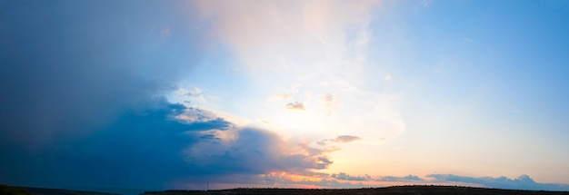 Красивый закат над сельской местностью с солнцем и облаками. изображение сшивается тремя кадрами.