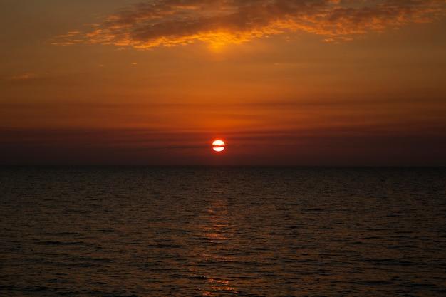 바다 위의 아름다운 일몰 바다 위로 지는 해, 저녁에 태양이 물 속으로 가라앉는다