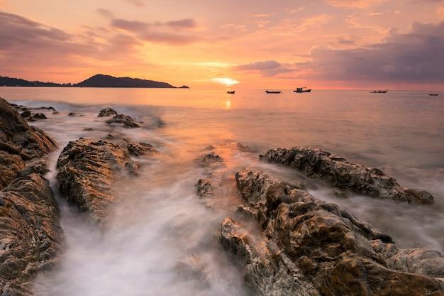 タイ、プーケットのカリムパトンビーチの美しい夕日アンダマン海景。夕暮れ時または薄明時の岩の動きの波。夏休みの有名な旅行先。