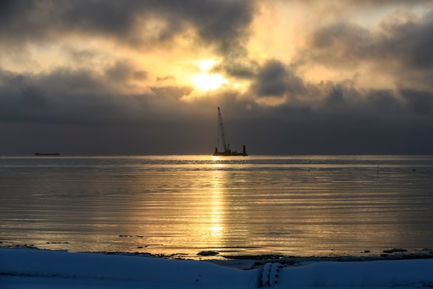 Beautiful sunset in arctic sea. barge with crane. golden hour. construction marine offshore works. dam building, crane, barge, dredger.