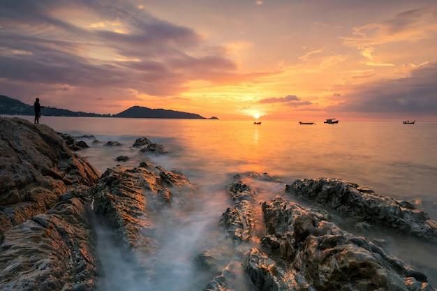 タイ、プーケットのカリムパトンビーチの美しい夕日。岩を通る動きの波で夕暮れ時に釣り。夕暮れの海景。夏休みの有名な旅行先。