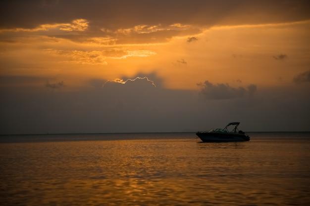 夕方の太陽の光の中で海のスピードボートで美しい夕日