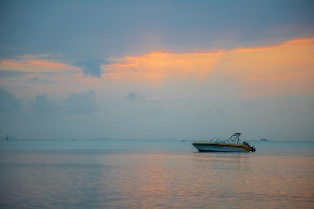 海の美しい夕日。夕方の太陽の光の中でスピードボート。