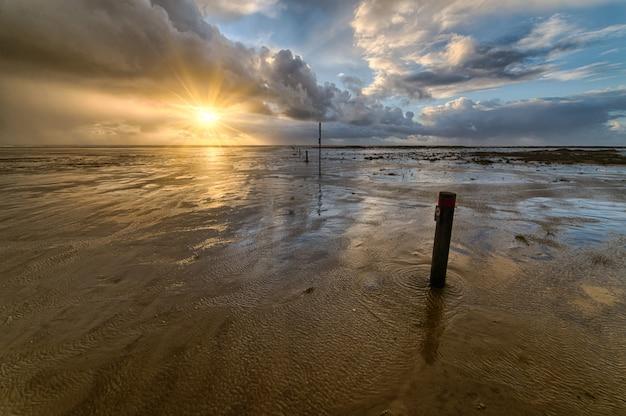 ビーチでの美しい夕日は、海岸での夜の散歩に最適な風景を作り出します