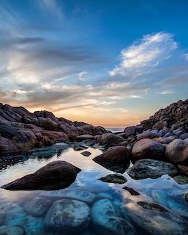 바위와 해변에서 아름 다운 석양