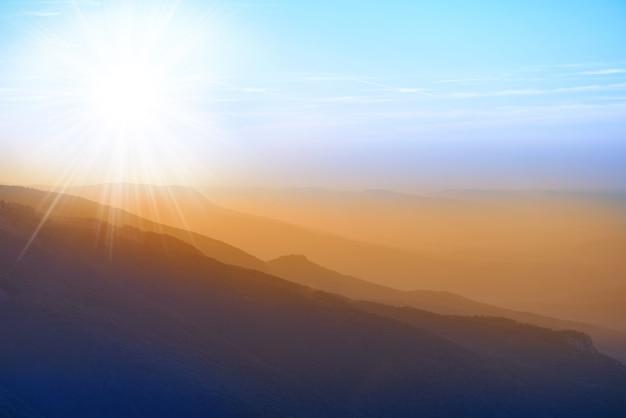 Красивый закат в горах. красочный пейзаж с солнечными лучами и голубым небом