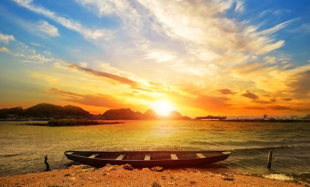Bellissimo paesaggio spiaggia al tramonto con una barca