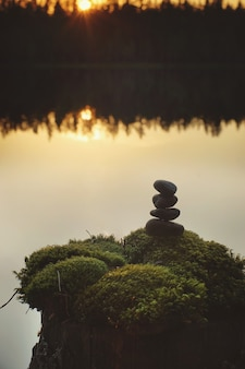 Beautiful sunset on a forest lake, a pyramid of stones on a stump overgrown with moss.