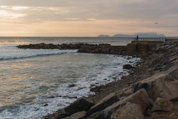 ペルーのリマの美しい夕日、明るい空、露出不足のビーチ