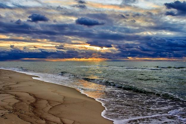 Красивый закат в облаках на берегу моря