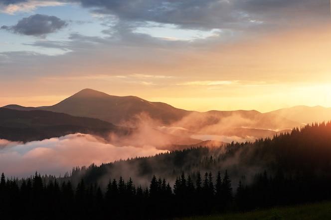 山の美しい夕日。オレンジ色の雲と霧を通して輝く太陽の光のある風景。