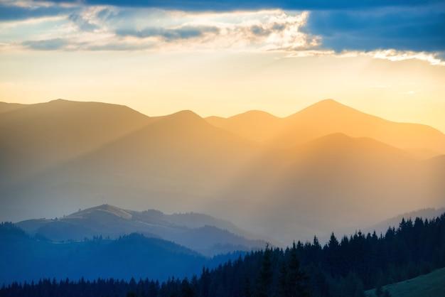 Красивый закат в горах. пейзаж с солнцем сквозь оранжевые облака