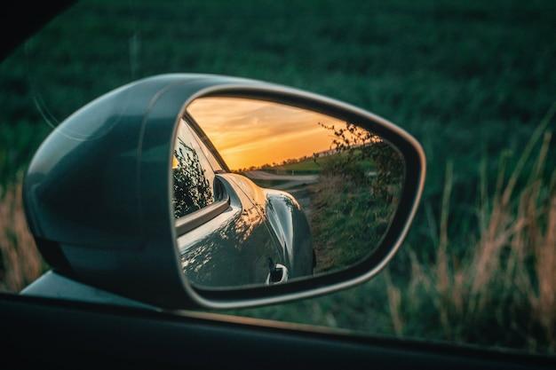 Красивый закат в зеркале бокового обзора автомобиля