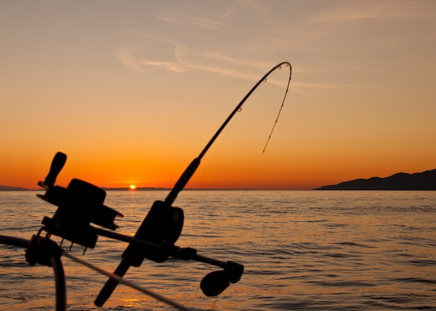Beautiful sunset landscape with a fishing rod