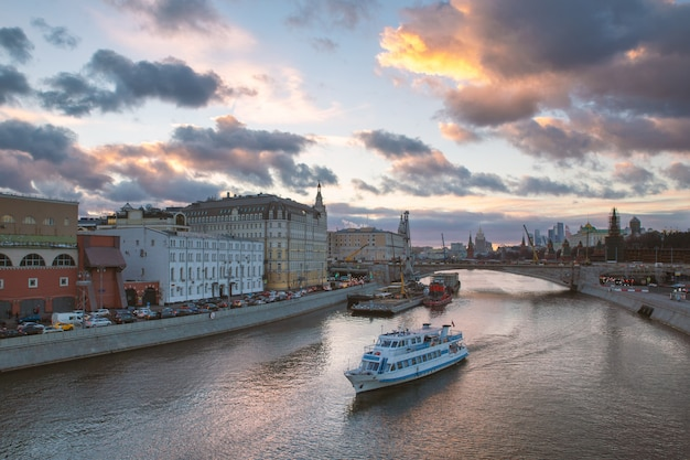Beautiful sunset over moskva river and a touristic boat cruising