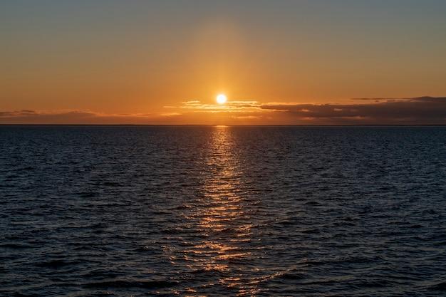 海に雲と空の美しい夕日。ゴールデンアワー照明。