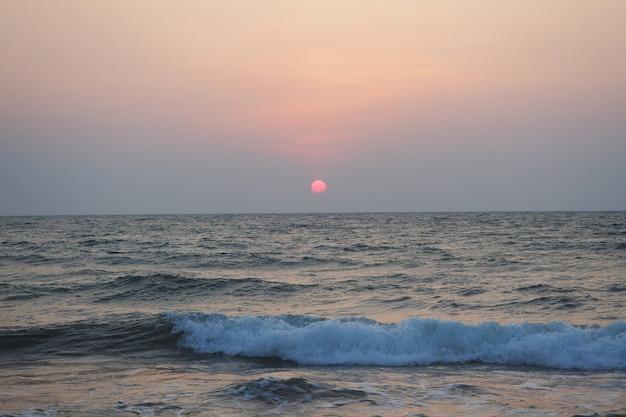 夏の海とビーチを背景に美しい夕日。休日と休暇の概念
