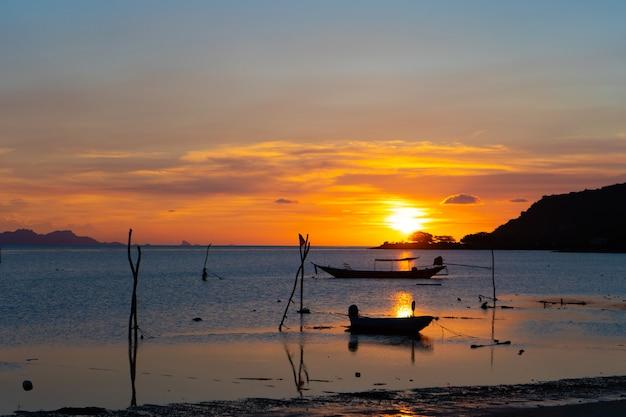 태국에서 열 대 섬, 바다에서 보트의 실루엣의 해 안에 아름 다운 석양.