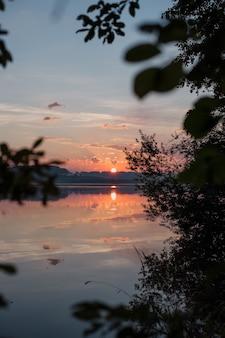 木々の間の湖に沈む夕日