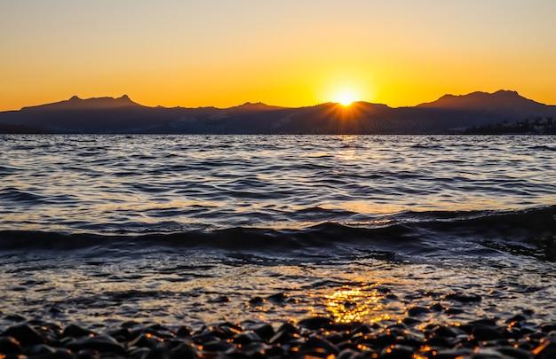 に照らされたビーチに島や山の石がある地中海沿岸の美しい夕日