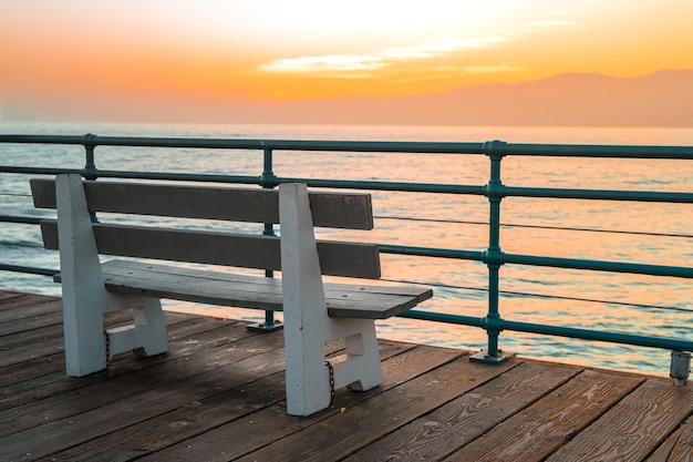 Красивый закат на берегу океана в калифорнии на пустой скамейке на деревянном пирсе