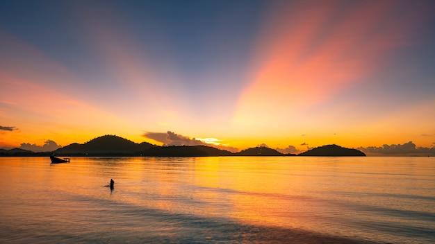 바다에서 어 부의 실루엣과 바다 위에 아름 다운 일몰 또는 일출 일몰 긴 노출 사진에서 산 배경 놀라운 풍경입니다.