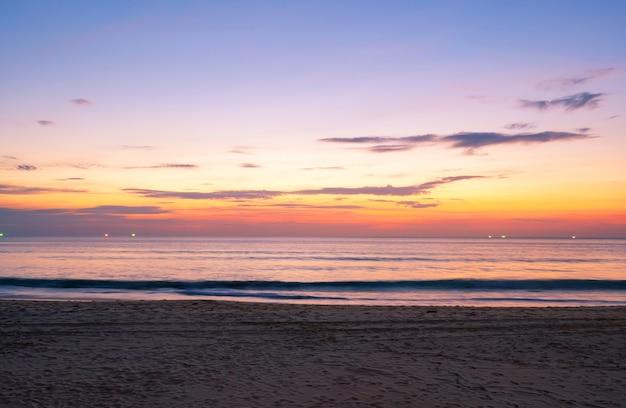 プーケットタイの前景に砂がある熱帯のビーチの熱帯の海に沈む美しい夕日または日の出。