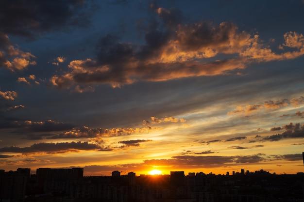 Красивый закат над большим городом с удивительными облаками
